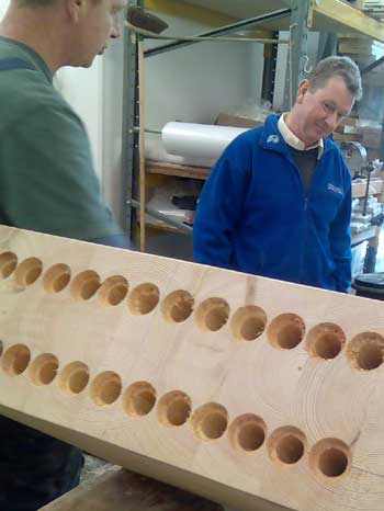 Clse up of large holes drilled into a laminated wood beam